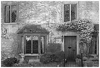 Stone house facade with flowers, Castle Combe. Wiltshire, England, United Kingdom (black and white)
