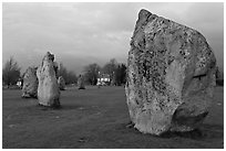 Standing stone circle and village house at dusk, Avebury, Wiltshire. England, United Kingdom (black and white)