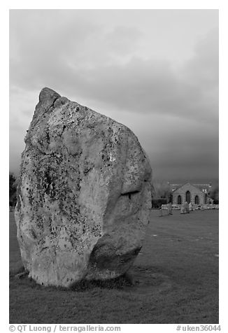 Standing stone and chapel at dusk, Avebury, Wiltshire. England, United Kingdom (black and white)