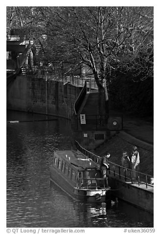 Family stepping out of houseboat onto quay. Bath, Somerset, England, United Kingdom (black and white)
