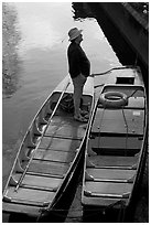 Man standing in a rowboat, old town moat. Canterbury,  Kent, England, United Kingdom (black and white)