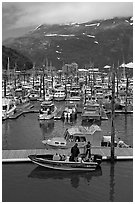 Small boat loaded at pier, harbor, and mountains. Whittier, Alaska, USA ( black and white)