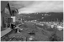 Couple sitting on bench by the harbor. Whittier, Alaska, USA ( black and white)