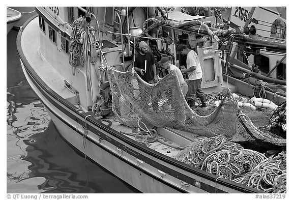 Fishermen repairing nets on fishing boat. Whittier, Alaska, USA (black and white)