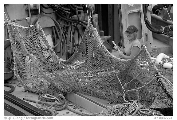 Woman repairing net on fishing boat. Whittier, Alaska, USA