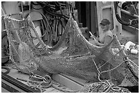 Woman repairing net on fishing boat. Whittier, Alaska, USA (black and white)
