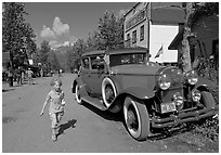 Girl on main street with red classic car. McCarthy, Alaska, USA (black and white)