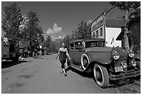 Woman walking next to red classic car. McCarthy, Alaska, USA (black and white)
