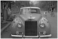 Rolls Royce on dirt road with mountain bikers in background. McCarthy, Alaska, USA (black and white)