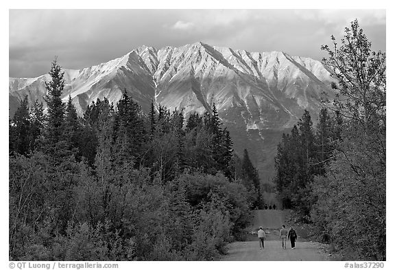 People walking on unpaved road, with last light on mountains. McCarthy, Alaska, USA (black and white)
