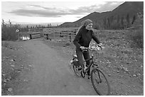 Woman on mountain bike with bridge behind. McCarthy, Alaska, USA (black and white)