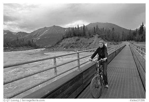 Woman on mountain bike crossing the footbridge. McCarthy, Alaska, USA (black and white)