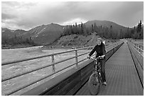 Woman on mountain bike crossing the footbridge. McCarthy, Alaska, USA ( black and white)