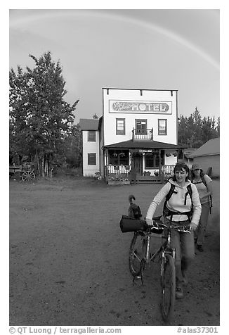 Women with bikes, hotel, and rainbow. McCarthy, Alaska, USA