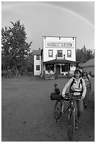 Women with bikes, hotel, and rainbow. McCarthy, Alaska, USA (black and white)