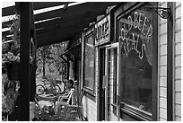 Man sitting in front of McCarthy lodge. McCarthy, Alaska, USA (black and white)