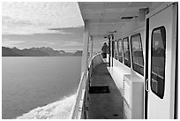 Passenger standing outside tour boat. Seward, Alaska, USA ( black and white)