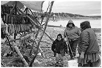 Inupiaq Eskimo family with stand of dried fish, Ambler. North Western Alaska, USA ( black and white)