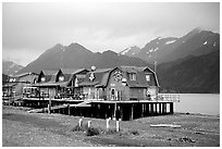 Stilt houses on the Spit, Kenai Mountains in the backgound. Homer, Alaska, USA (black and white)