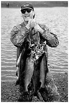 Man carrying salmon freshly caught in the Fishing Hole. Homer, Alaska, USA ( black and white)