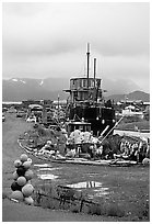 Retired fishing boat with a pile of marine gear on the Spit. Homer, Alaska, USA (black and white)