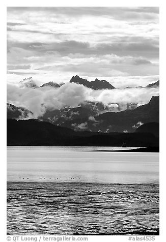 Low clouds hanging over Kenai Mountains across Katchemak Bay. Homer, Alaska, USA (black and white)