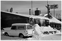Old truck parked next to lodge in winter. Alaska, USA ( black and white)