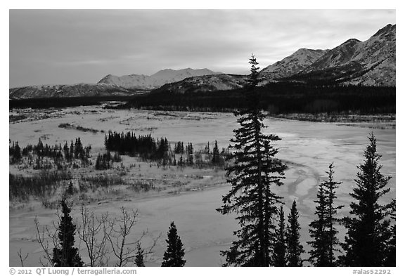 Winter landscape with frozen river at sunset. Alaska, USA (black and white)