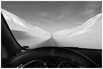 Road in wintry landscape seen from dashboard indicating -32F temperature. Alaska, USA (black and white)