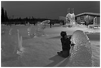 Child amongst ice sculptures at dusk. Fairbanks, Alaska, USA ( black and white)