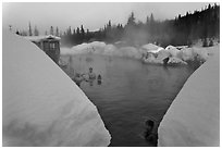Soaking in natural hot pool surrounded by snow. Chena Hot Springs, Alaska, USA ( black and white)