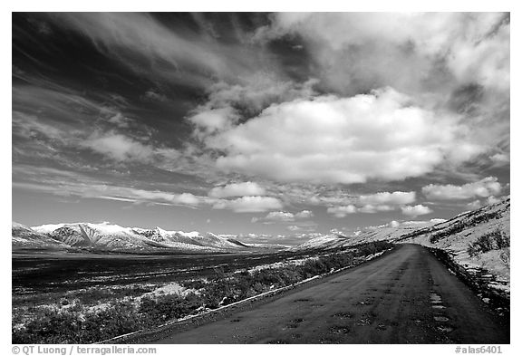 Gravel road under large white clouds. Denali Highway, Central Alaska,