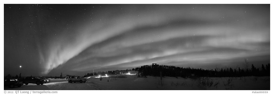 Northern Lights streaking above cars and cabin at Cleary Summit. Alaska, USA (black and white)