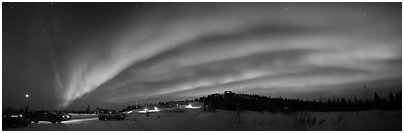 Northern Lights streaking above cars and cabin at Cleary Summit. Alaska, USA (Panoramic black and white)