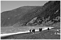 Backpackers on black sand beach and King Range, Lost Coast. California, USA ( black and white)