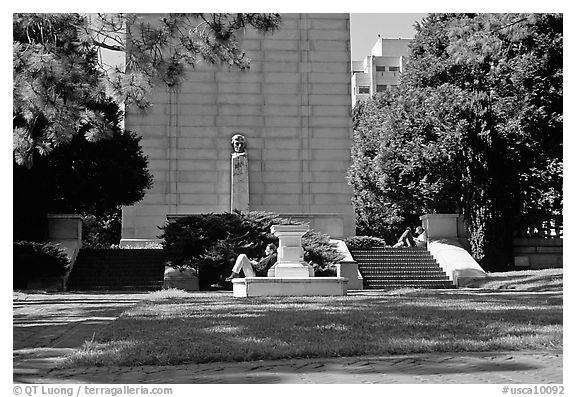 Reading at the base of the Campanile on the UC Campus. Berkeley, California, USA (black and white)
