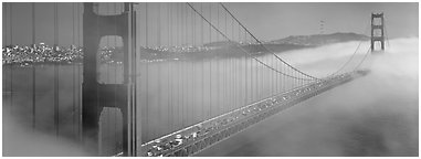 Fog rolling over Golden Gate Bridge. San Francisco, California, USA (Panoramic black and white)