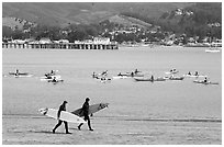 Surfers and sea kayakers, Pillar point harbor. Half Moon Bay, California, USA ( black and white)