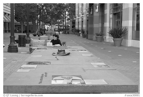 Woman sitting at a commemorative table in a downtown alley. San Jose, California, USA (black and white)