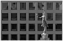 Statue on Admiral Dewey memorial column in front of modern building. San Francisco, California, USA ( black and white)