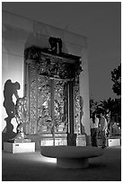 A couple contemplates Rodin's Gates of Hell at night. Stanford University, California, USA (black and white)
