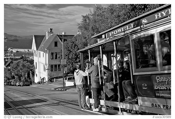 Cable car plunging with people clinging on Hyde Street, late afternoon. San Francisco, California, USA (black and white)
