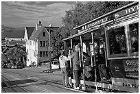 Cable car plunging with people clinging on Hyde Street, late afternoon. San Francisco, California, USA ( black and white)