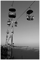 Sky glider Riders enjoy the last sunrays of the day. Santa Cruz, California, USA (black and white)