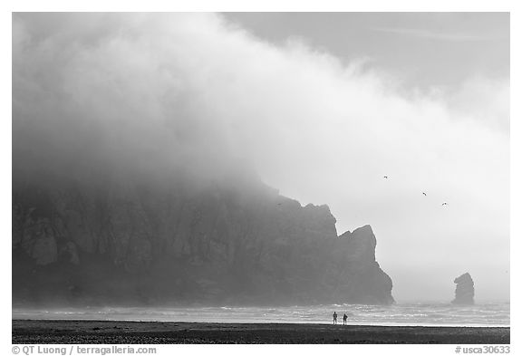 Two people strolling on the beach at the base of Morro Rock. Morro Bay, USA (black and white)