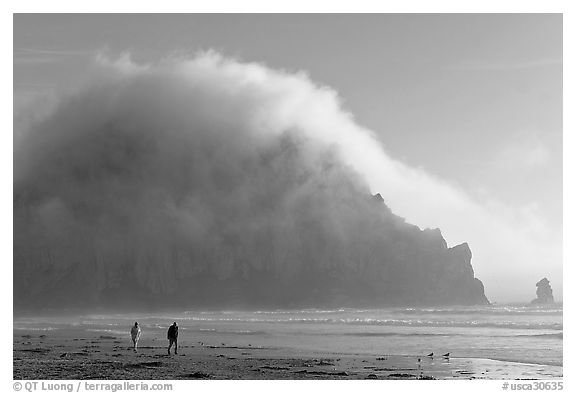 Couple walking on the beach, with Morro Rock and fog behind. Morro Bay, USA (black and white)