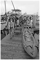 Sea kayaks and passengers awaiting loading on tour boat. California, USA (black and white)