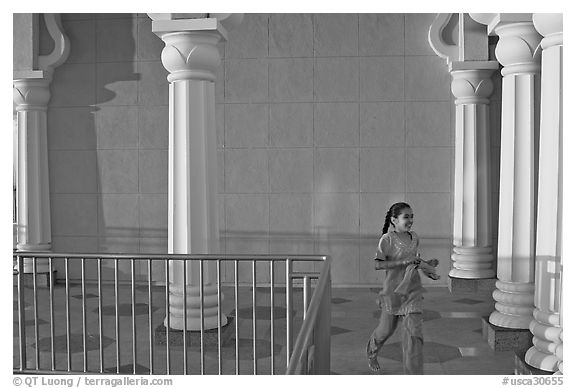 Indian girl running in the Sikh Gurdwara Temple, late afternoon. San Jose, California, USA (black and white)