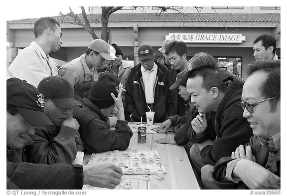 Vietnamese immigrants at a Chinese chess game. San Jose, California, USA (black and white)