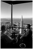 Businessmen with a bottle of Champagne in the Carnelian Room with panoramic view of the City. San Francisco, California, USA ( black and white)